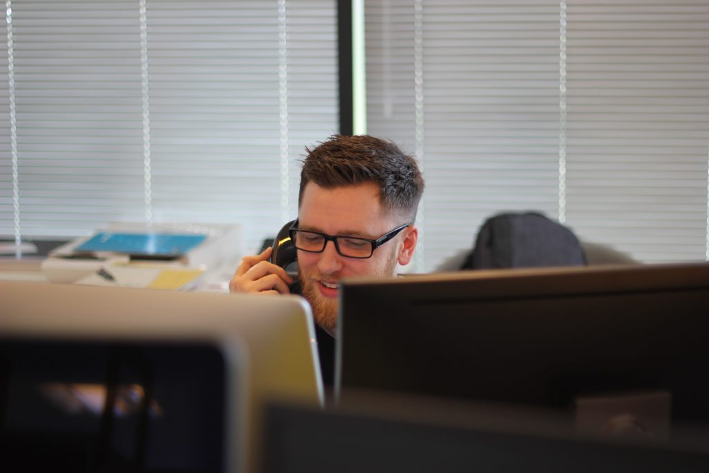 A man with glasses in his office desk facing two work monitors is talking on the telephone