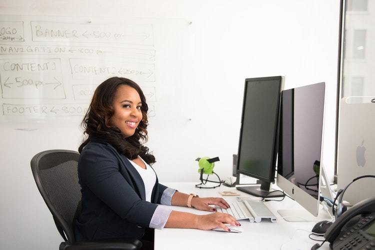 A woman in business attire smiling while she is seated across her desktop computer with her arms on the keyboard and mouse